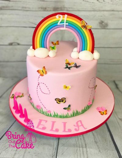 4th birthday cake with rainbow topper and butterflies