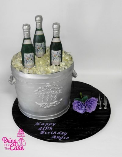 Silver champagne ice bucket cake with edible chocolate bottles and candy ice cubes. Silver, black and purple theme